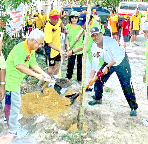 Rotary President Ng (l) together with Mayor Roshidi (r) planting a Tree.
